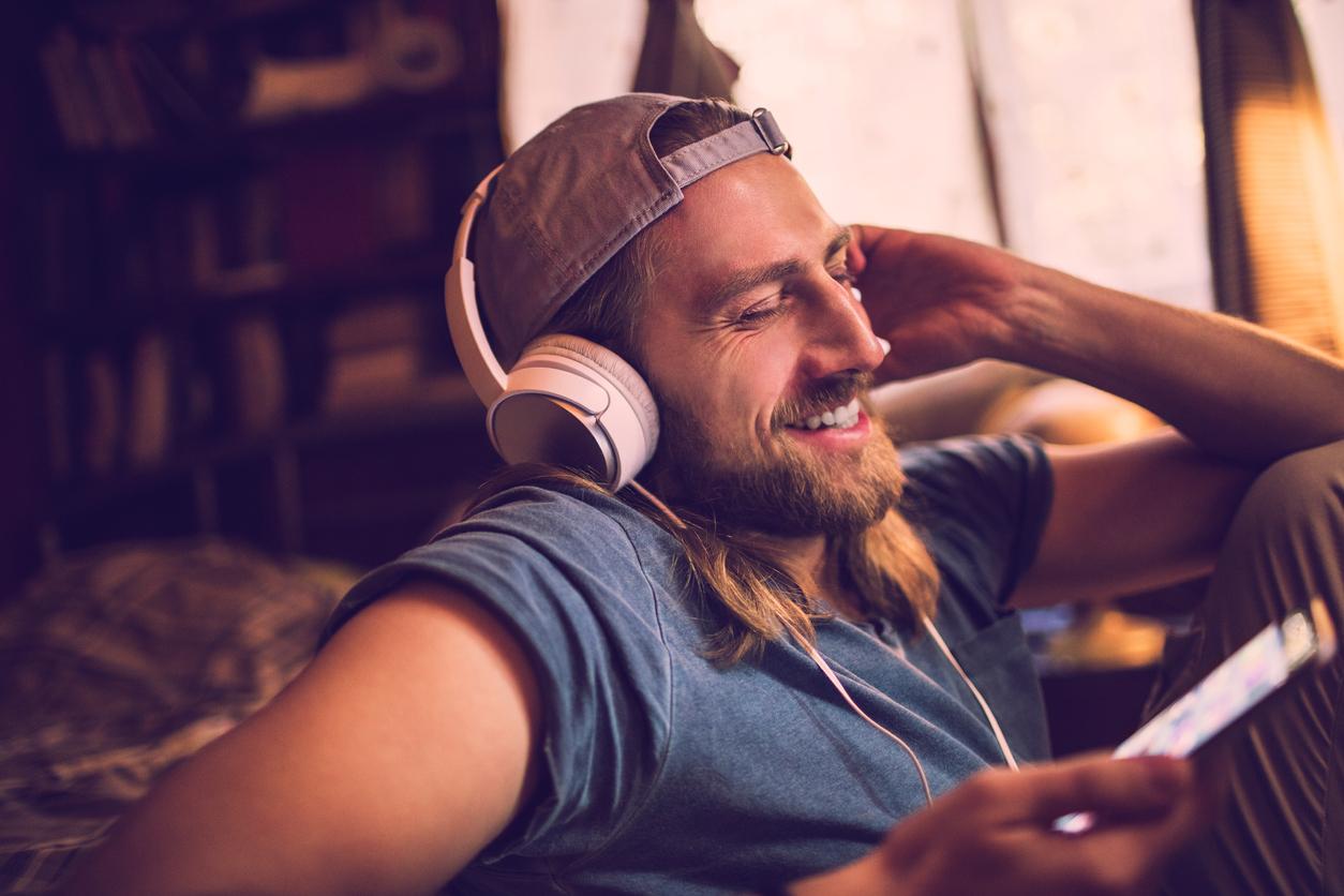 man laughing while listening to podcast