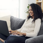 young woman using laptop on couch at home