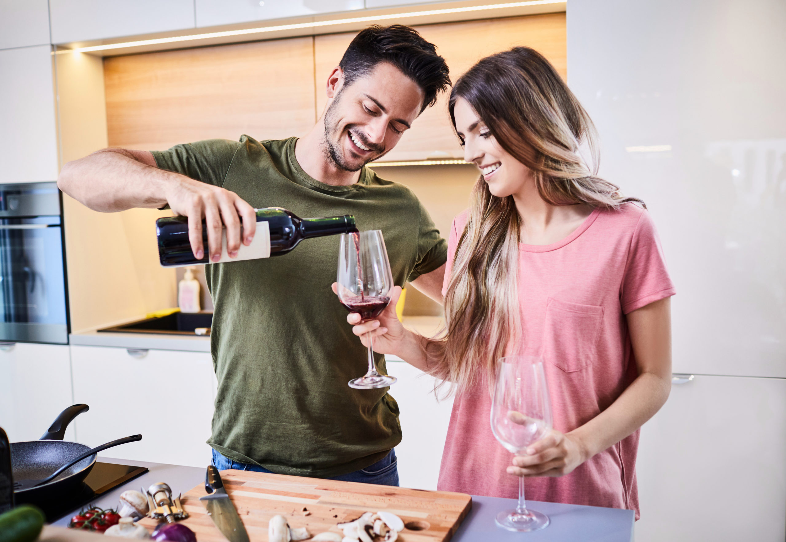 Young man pouring a glass of wine for his girlfriend in the kitchen