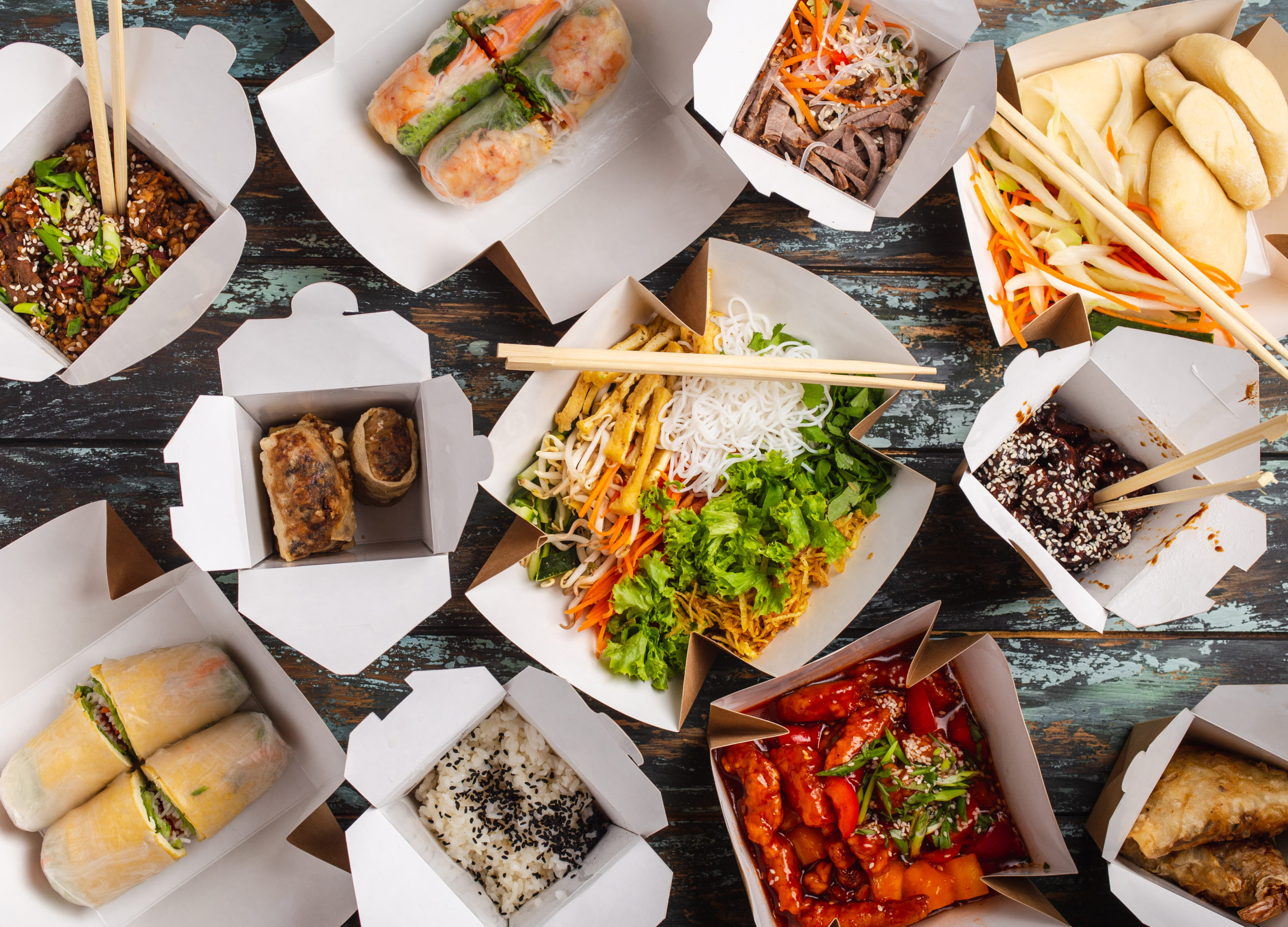 Assorted Chinese dishes in paper delivery boxes seen from above