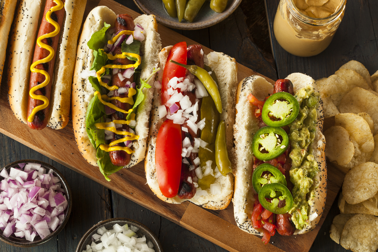 row of gourmet hot dogs on a wooden board