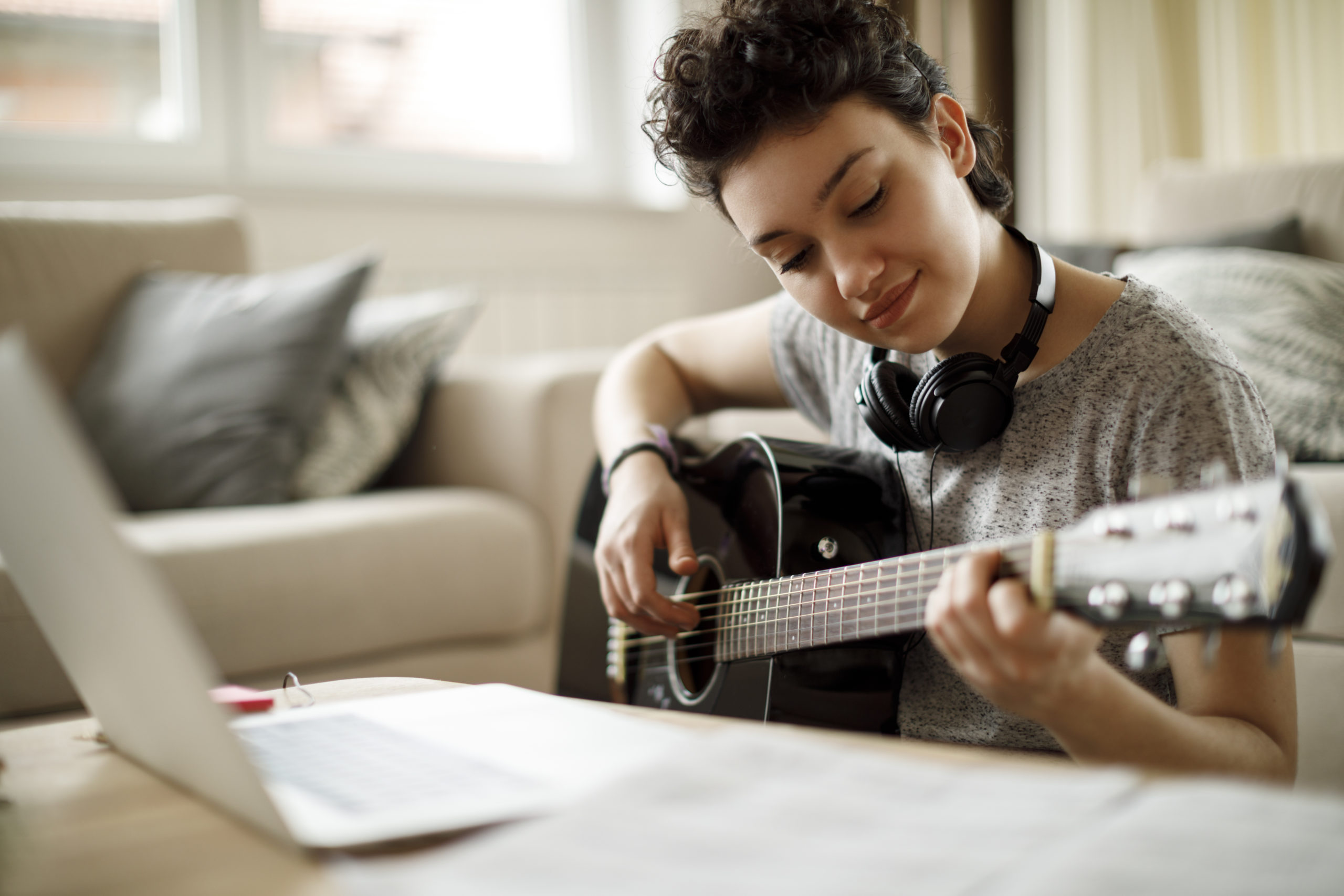 girl learning to play guitar with online music classes