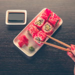 woman's hand picking up a sushi roll with chopsticks