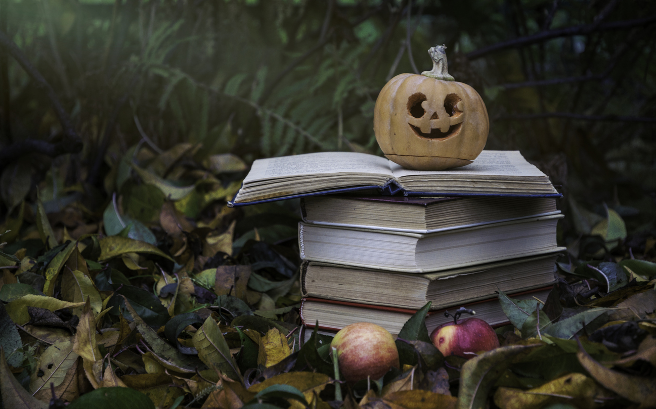 stack of books with a pumpkin on top