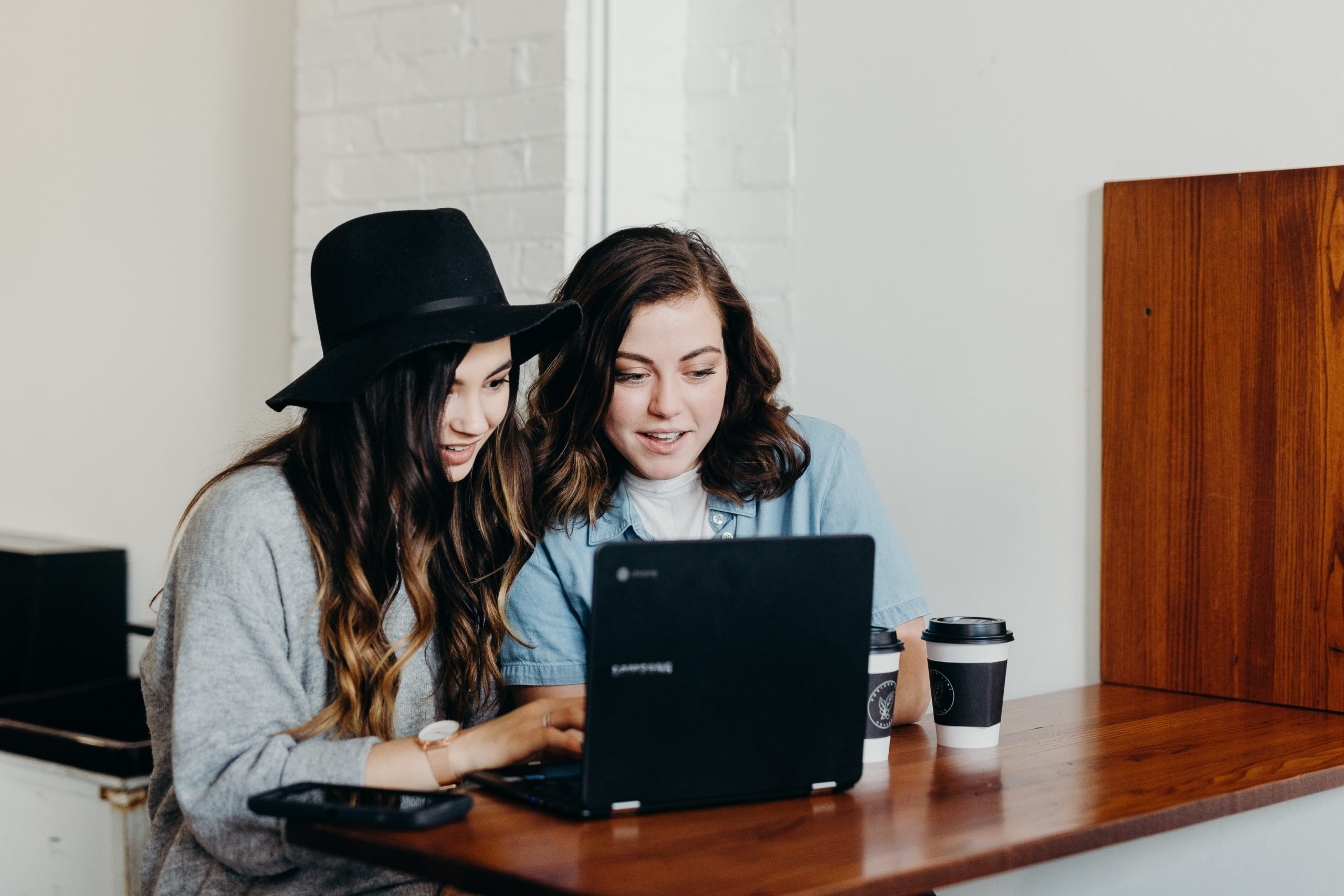 two girls working on a laptop