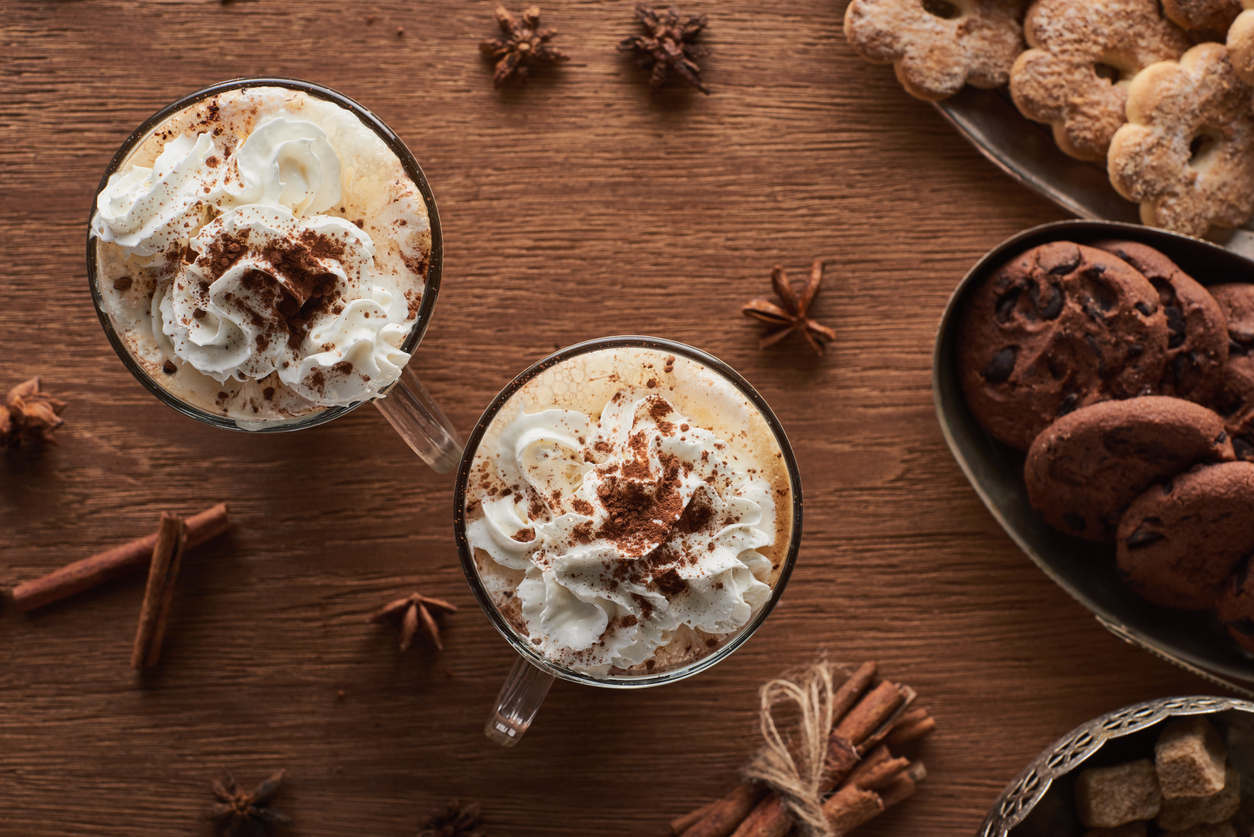 mugs of hot chocolate with whipped cream on a table.