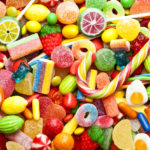 Top view of colorful candies, jellybeans and lollipops