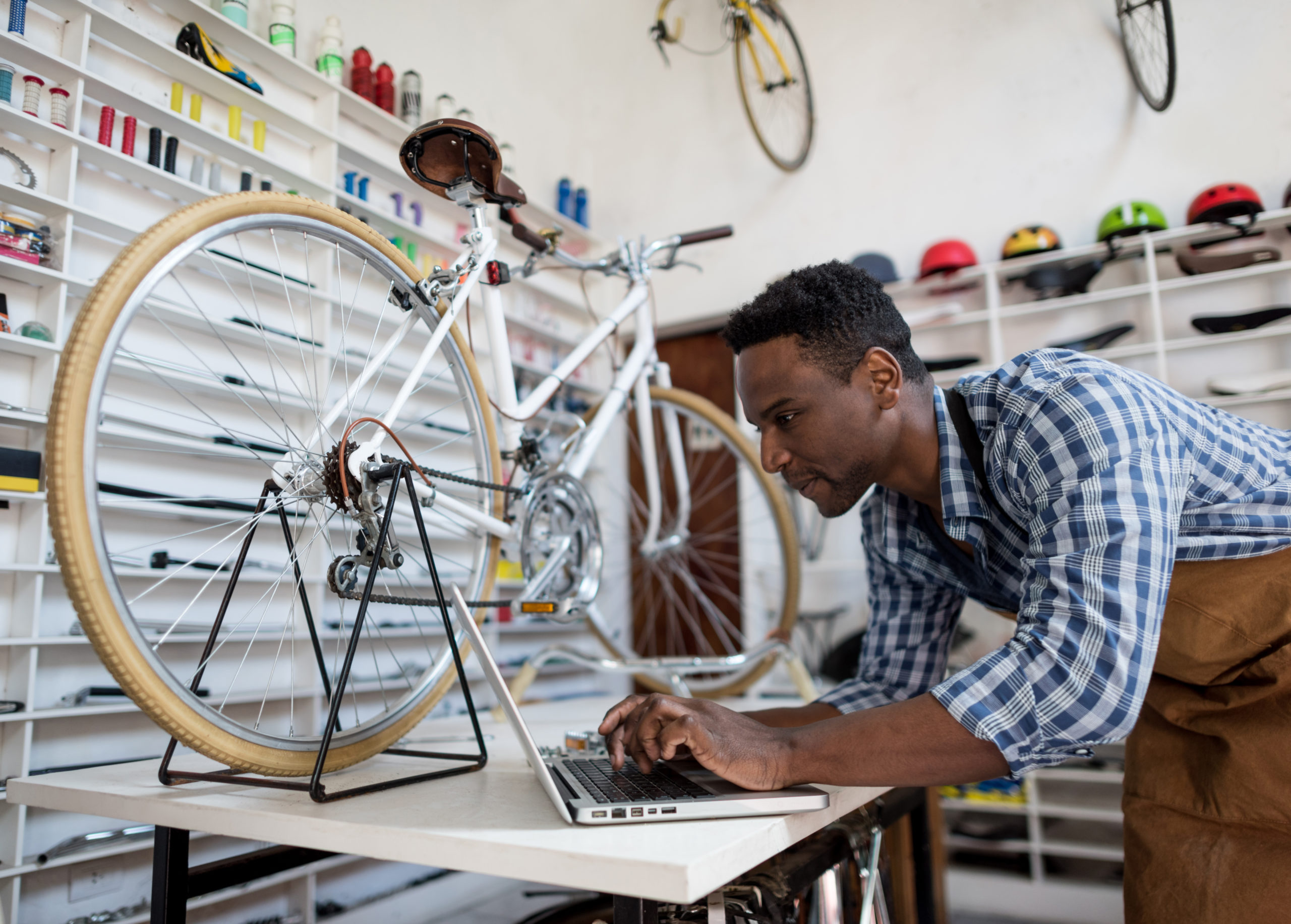 A man working on a bike in his shop.
