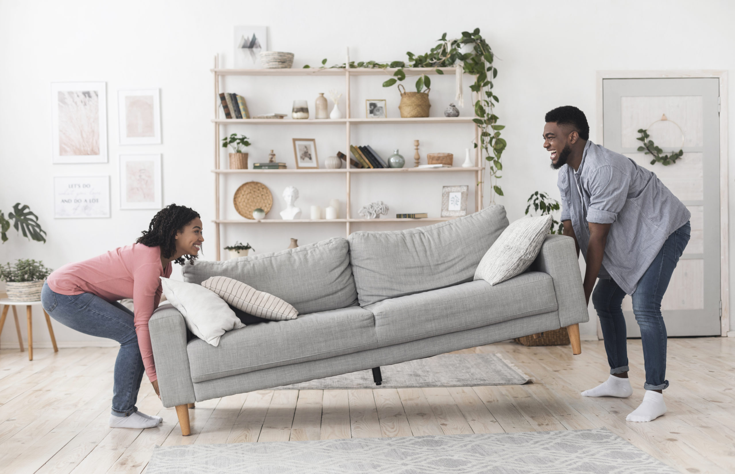 Young couple replacing their living room couch | Hanover furniture stores offering online shopping