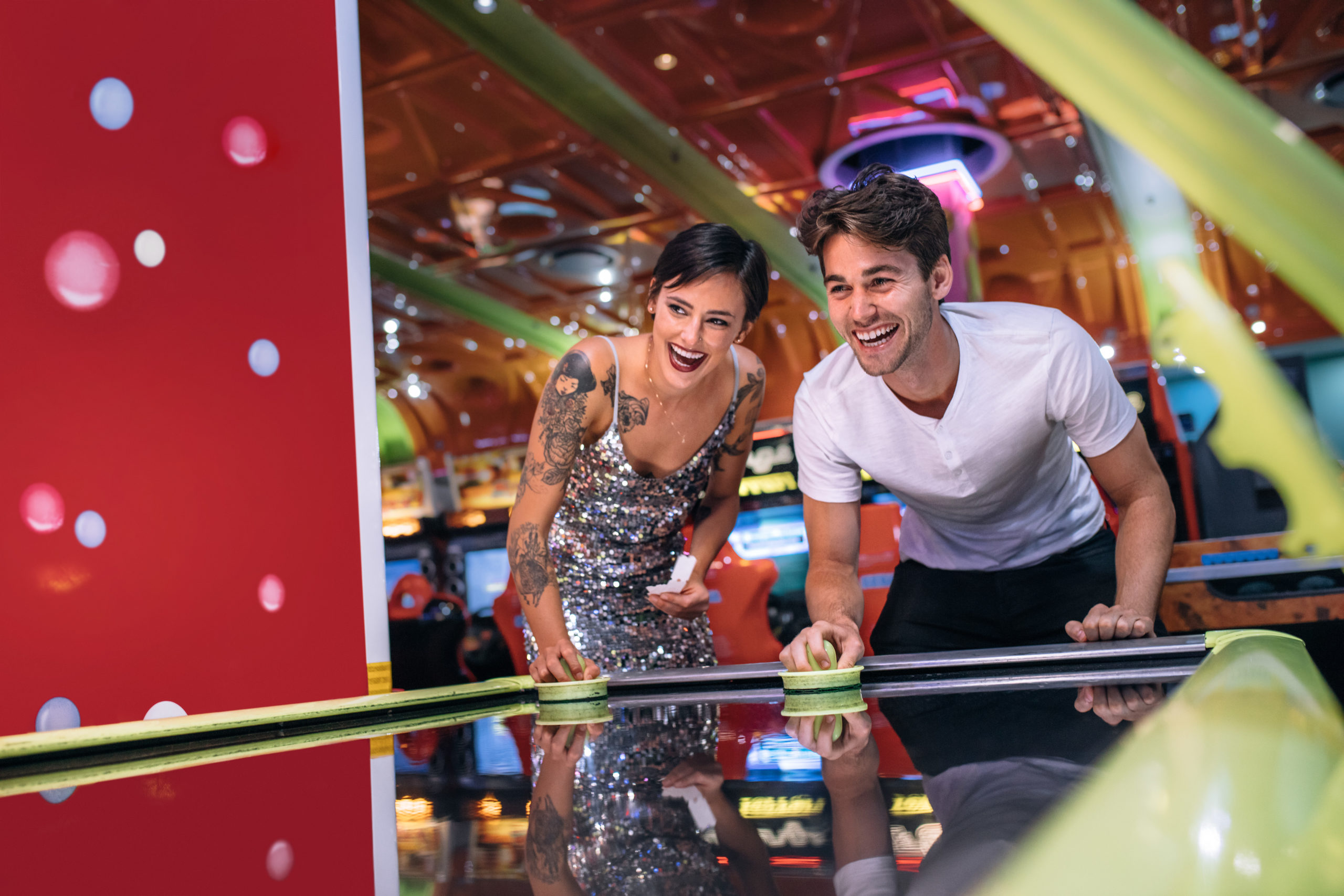 Friends playing air hockey at a gaming parlor | things to do in Hanover, MD
